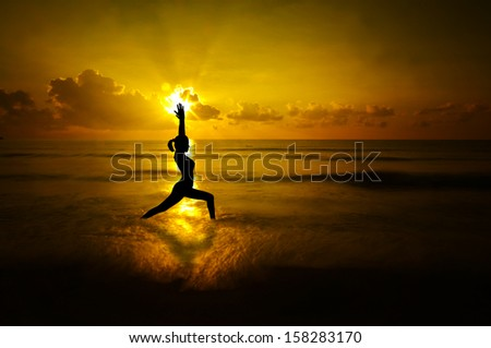 Silhouette of female doing yoga meditation during sunrise with natural golden sunlight at beach. - stock photo
