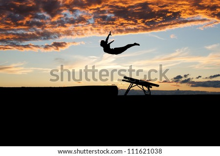silhouette of female gymnast jumping on mini trampoline in sunset - stock photo