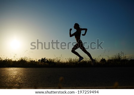 Silhouette of female runner in the action jogging down the road at sunset