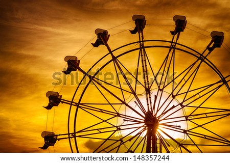 Silhouette of ferris wheel at sunset during summer at county fair - stock photo