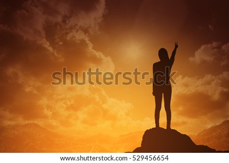 silhouette of fighting woman at sunset or sunrise standing and raising up her hand and two finger in celebration of having reached mountain top summit goal.Happy celebrating.business success concept