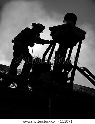 Silhouette of fire fighter on roof top - black and white