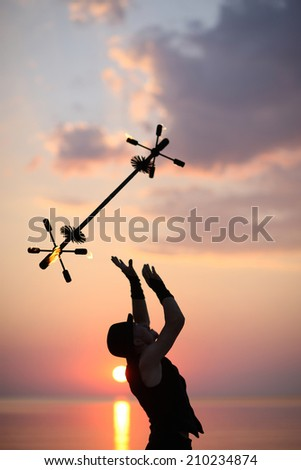 Silhouette of fire magician juggling with a fire baton - stock photo