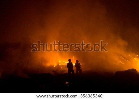Silhouette of fireman fighting bushfire at night. - stock photo