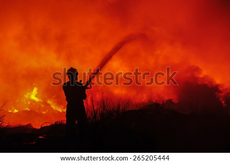 Silhouette of fireman fighting bushfire at night. Image is soft and contain noise due to high ISO used. - stock photo