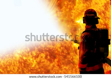 Silhouette of Firemen fighting a raging fire with huge flames of burning with work space  Elements of this image are furnished by NASA