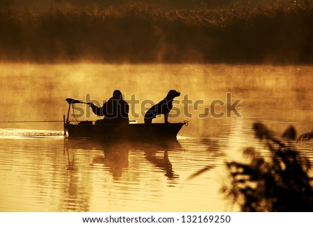 Silhouette of fisher and dog sitting in boat - stock photo