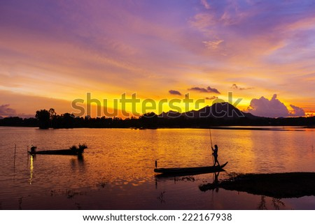 Silhouette of fisherman and traditional thai boats at sunset beach. Ao Nang, Krabi province. - stock photo