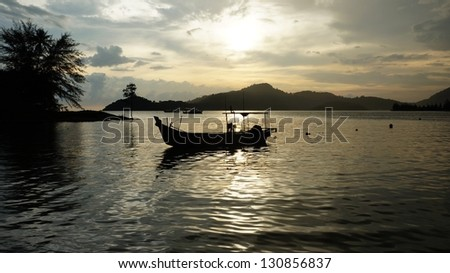 silhouette of fisherman boat in sunset at Perak, Malaysia.