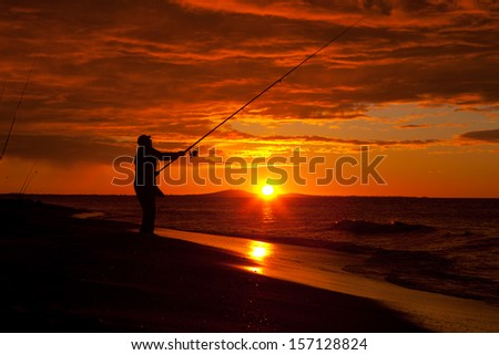 silhouette of fisherman by the ocean in sunrise