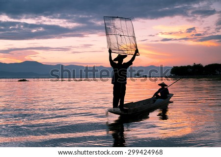 Silhouette of fisherman is traditional thai fishing style,  sunset time, at Kwan Phayao lake, Phayao province, Thailand