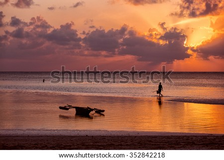 Silhouette of fisherman on boat at a beautiful sunrise with colorful clouds - stock photo