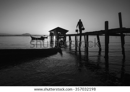 Silhouette of fisherman walk on wooden jetty during sunrise in black and white format. - stock photo