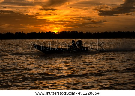 Silhouette of fishermen and long tail boat in the sea with beautiful sunlight background at Suratthani, Thailand.