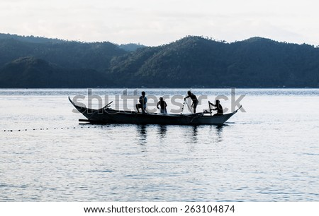 silhouette of fishermen on the fishing boat - stock photo