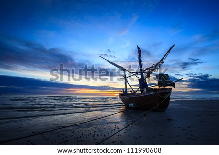 silhouette of fishermen with sunrise in the background - stock photo