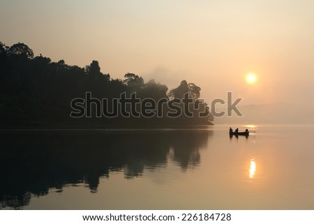 Silhouette of fishermen with thier boat fishing in the mist at morning light on lake