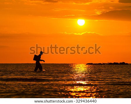 Silhouette of fishermen with yellow and backrgound. - stock photo