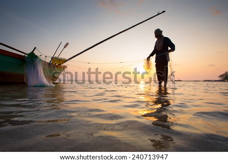 silhouette of fishermen with yellow and orange sun in the background