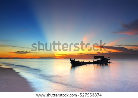 Silhouette of fishing boat abandoned with beautiful sunrise in the eastern at Gulf of Thailand