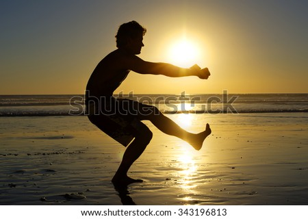 Silhouette of fit shirtless man doing one leg air squat on beach with beautiful sunset