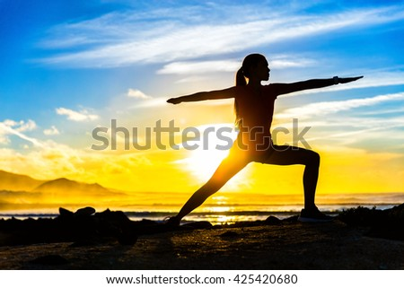Silhouette of fitness athlete practicing warrior II yoga pose meditating at beach sunset. Woman stretching doing morning meditation against colorful sky background. Zen wellness and wellbeing concept. - stock photo