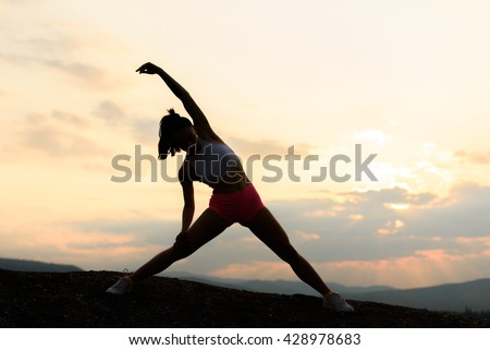 Silhouette of fitness woman exercising and stretching on beautiful summer sunset or morning at beach. Female doing relaxing yoga exercises
