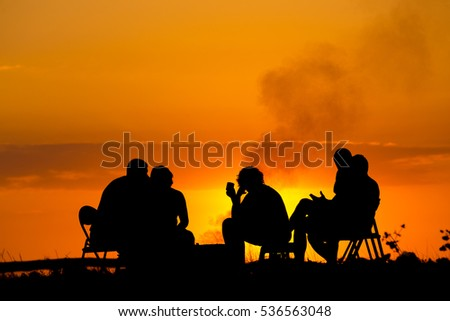 silhouette of five people in camping sitting near campfire against sunset