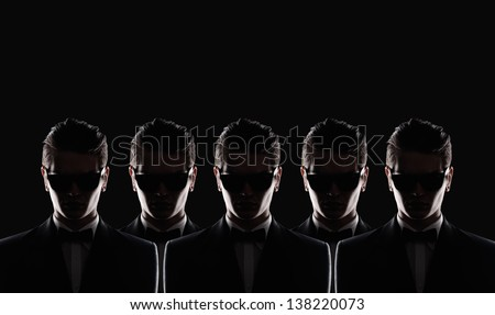 silhouette of five young men in a jacket on a black background in studio