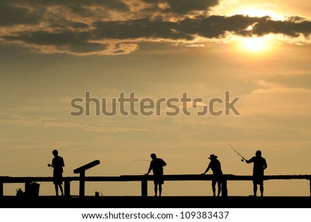Silhouette of four fisherman at sunset