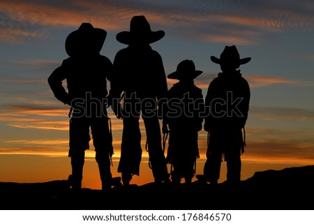 Silhouette of four young cowboys sunset background - stock photo