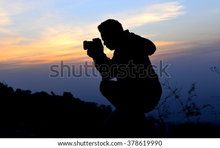 silhouette  of freedom photographer action with camera in sun set time on the mountain view