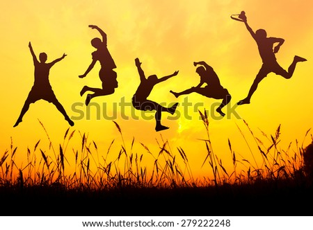 silhouette of friends jumping in sunset - stock photo