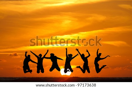 silhouette of friends jumping in sunset at beach - stock photo