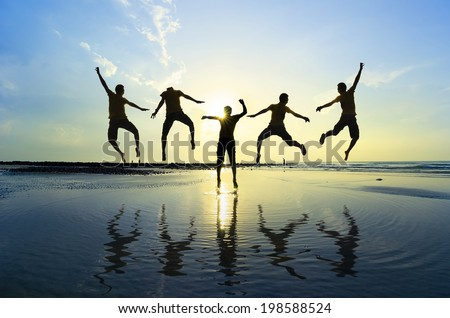 Silhouette of friends jumping over sun rising up - stock photo