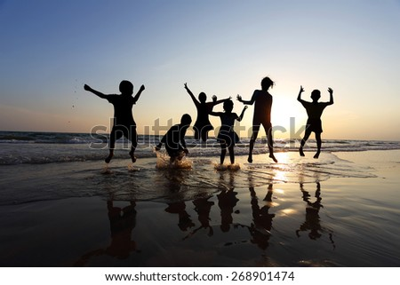 Silhouette of friends of the children jumping on the beach at the sunset time