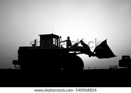 Silhouette of front end loader and worker in construction site at oilfield - sunset - black and white