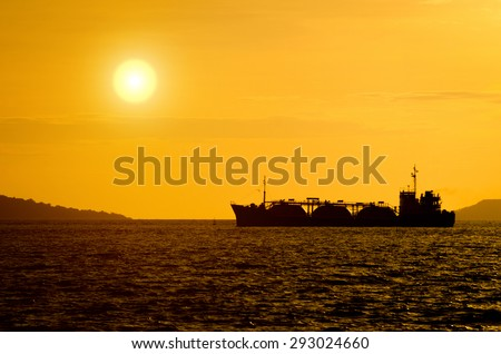 Silhouette of gas tanker in the sea at sunset - stock photo