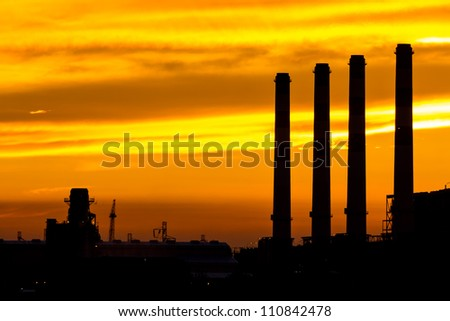 Silhouette of gas turbine electrical power plant at dusk - stock photo