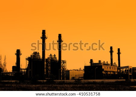 Silhouette of gas turbine electrical power plant at sunset - stock photo