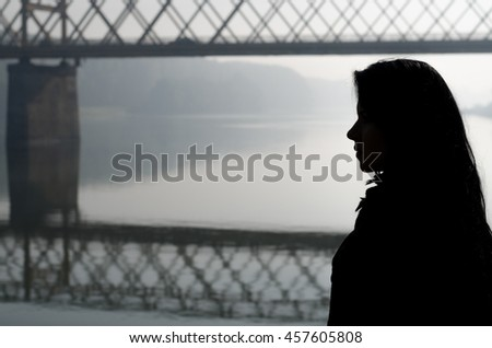 Silhouette of girl and bridge over river on beautiful autumn day.