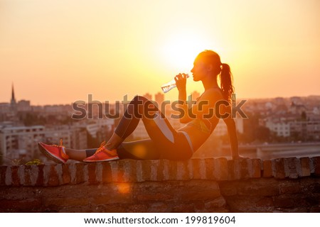 silhouette of girl drinking water outdoor - stock photo