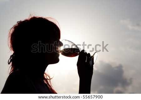 Silhouette of girl drinking wine