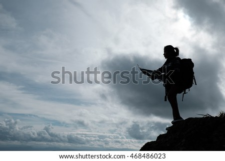 Silhouette of Girl Hikers with backpack and map on the mountain.