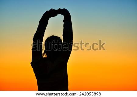 Silhouette of girl in sunset - stock photo