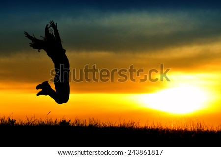 Silhouette of girl jumping in sunset.