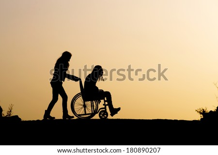 Silhouette of girl on a wheelchair and helping a friend