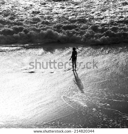 silhouette of girl on beach in breaking waves  - stock photo