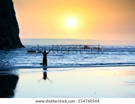 Silhouette of girl standing in waves, arms raised in praise to God at sunset - stock photo