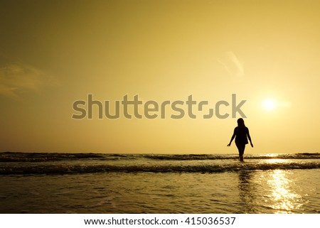 Silhouette of girl walking at the beach during sunset with copy space area. Soft focus due to shot at dusk.